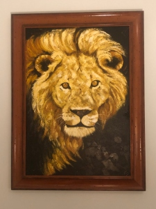 Tanzanian painting of a lion looking straight ahead. Symbolic of Compassion..