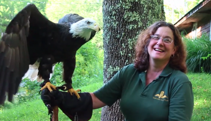 Season {2} Episode {5}: Wendy Perrone Image shows smiling woman holding a bald eagle with its wings slightly raised.
