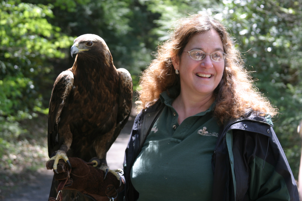 Season {2} Episode {5}: Wendy Perrone Image shows a smiling woman holding a large raptor