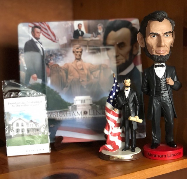 Photo of a few of the presidential collectibles on Teddie's bookshelf including an Abraham Lincoln bobblehead and figurine.